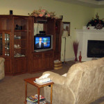 Living room at West Linn care home showing couches, corner fireplace, and entertainment center with TV