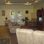 Living room at West Linn Care Home with lots of couches and a glass door that leads out to the patio