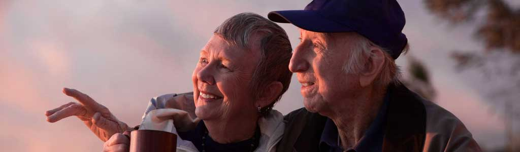 Happy senior couple watching sunset.