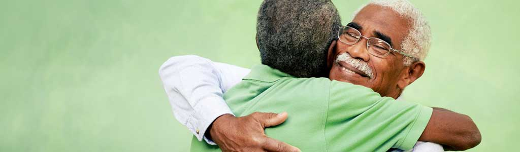 Two senior men hugging.