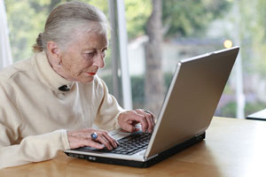 Elderly woman working on laptop computer
