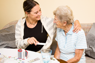 Nurse dispensing medication to elderly woman