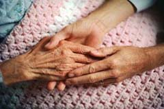 Image of caregiving holding hands with elderly woman