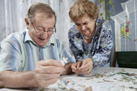 Older couple working on jigsaw puzzle together